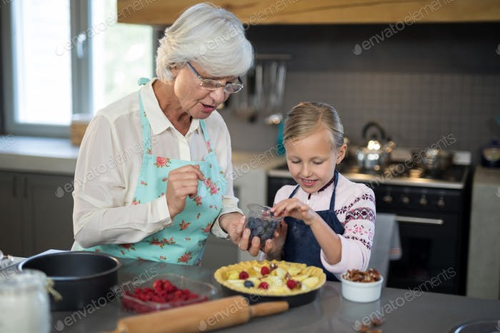 Grandmother and granddaughter adding blue berries to the crust