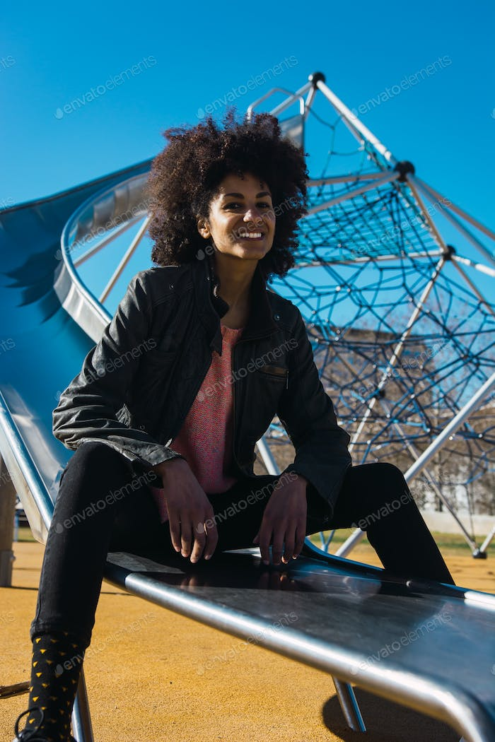 Woman with afro hair jumping down a slide.