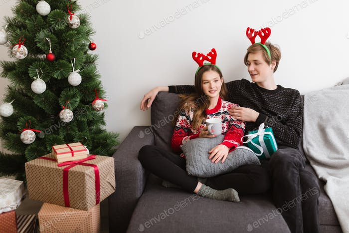 Young beautiful couple sitting on sofa at home and wearing deer horns near Christmas tree