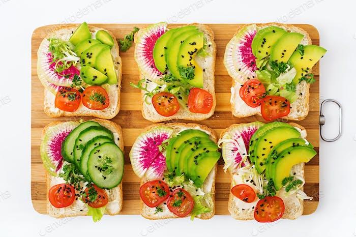 Vegan sandwiches with avocado, watermelon radish and tomatoes