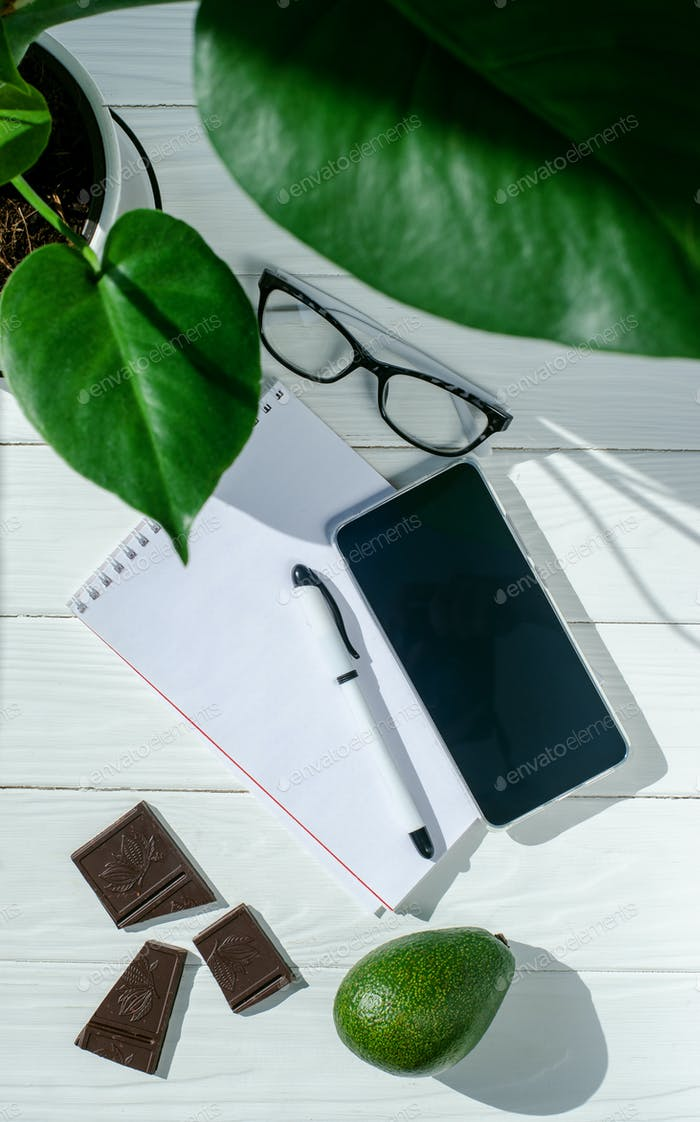 Notebook, pen, glasses and flower in a pot, chocolate and avocado on the white wooden table.
