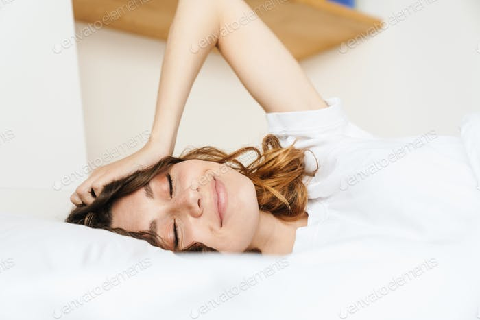 Image of happy woman smiling while lying in bed on white pillow