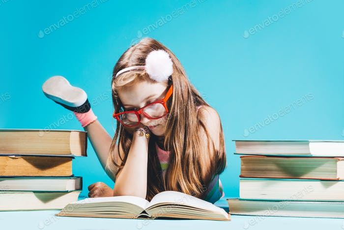 Little girl sitting by the books, studying.
