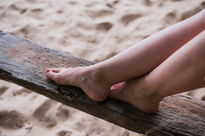 woman hands and legs close up on a piece of wood outdoors