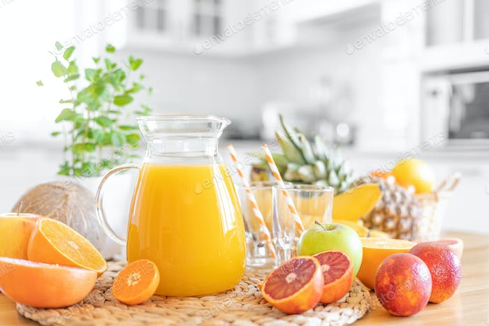 Multifruit juice and fresh fruit on table on kitchen background closeup