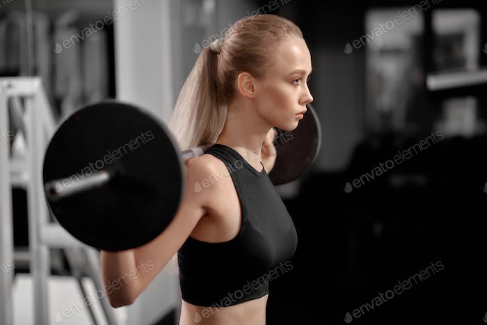 Athletic, beautiful girl in sportswear working out in gym