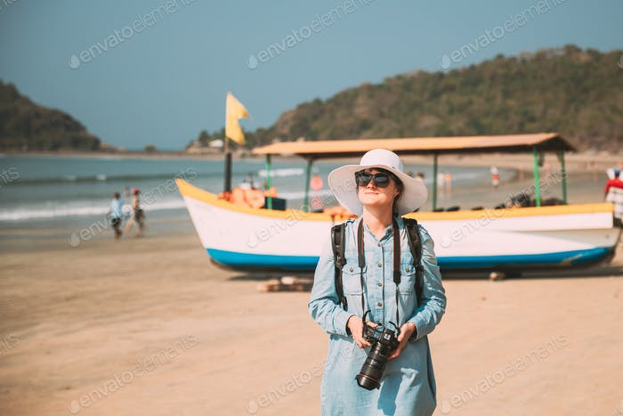 Canacona, Goa, India. Young Caucasian Lady Woman With Camera Standing On Famous Palolem Beach Near