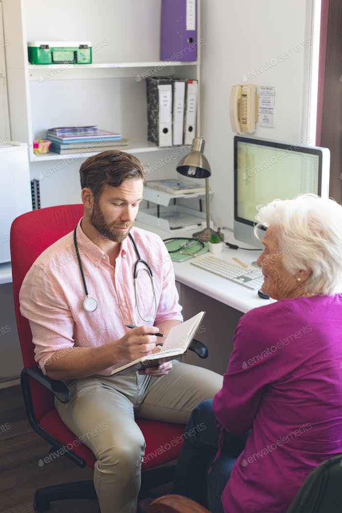 Male Doctor writing prescription on notebook to senior woman in clinic room