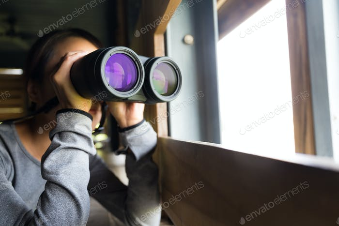 Asian woman use of the binoculars for birdwatching