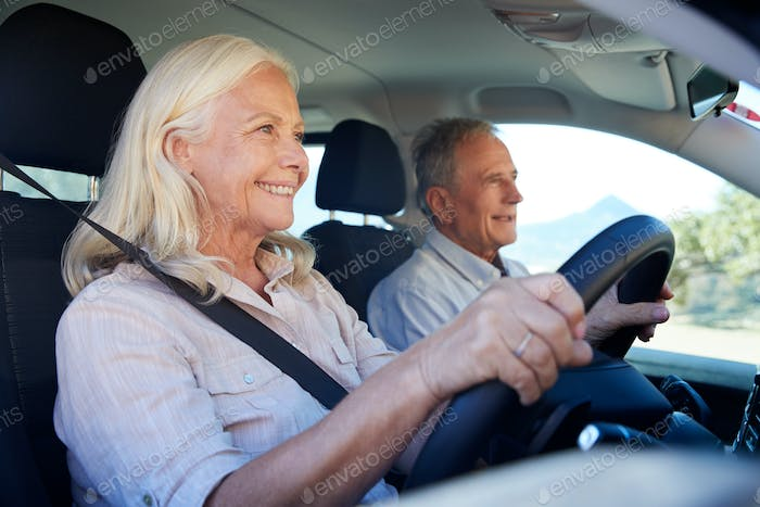 Senior white woman driving car, her husband beside her in front passenger seat, close up, side view