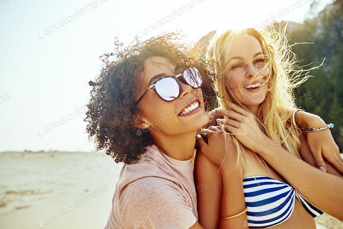 Two girlfriends laughing while walking along a sandy beach