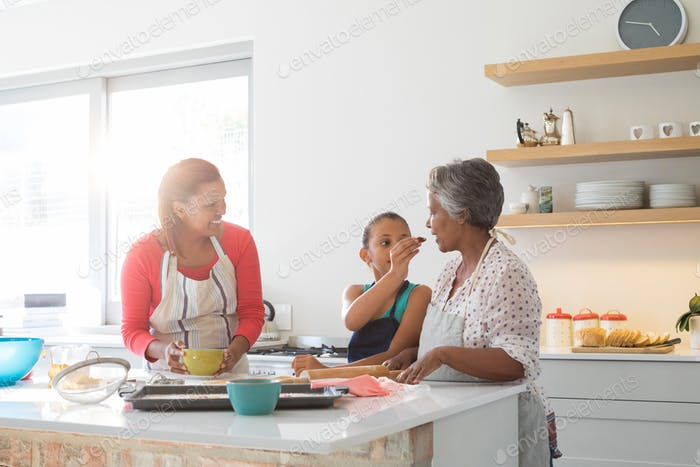 Girl feeding food to her grandmother in kitchen