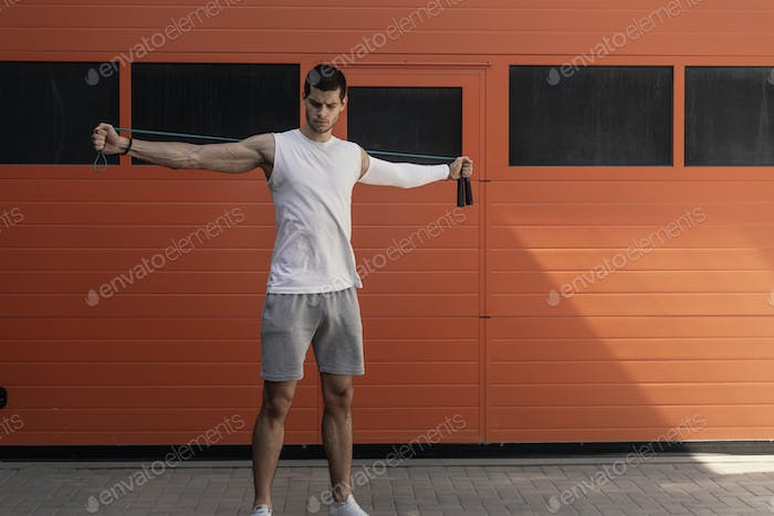 Portrait of muscular young man exercising, stretching with jumping rope