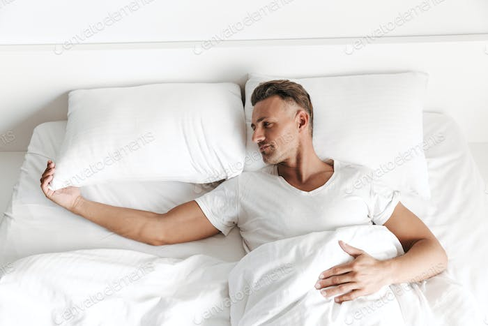 Sad man laying in bed and looking away