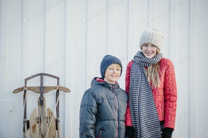 Ein Bruder und eine Schwester nebeneinander in einem Hof im Winter.
