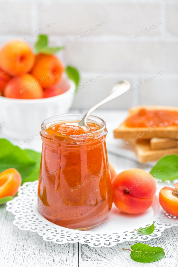 Apricot jam in a jar and fresh fruits with leaves on white wooden table, breakfast