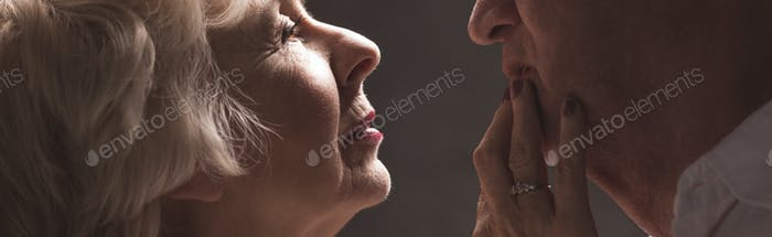 Elderly woman touching husband's lips