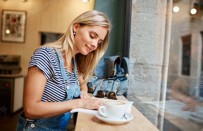 Beautiful young pregnant girl sitting in cafe reading magazine a