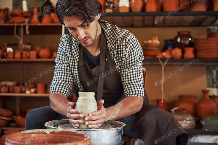 Ceramist uses potter's wheel and creates a handmade clay product