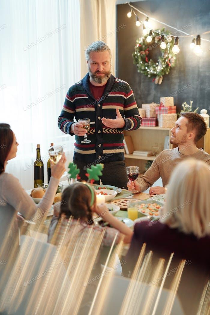 Hombre barbudo con bebida haciendo tostadas de Navidad frente a su familia por la mesa servida