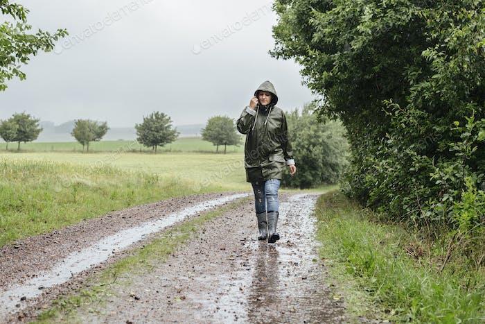 Mujer caminando por el camino de tierra bajo la lluvia