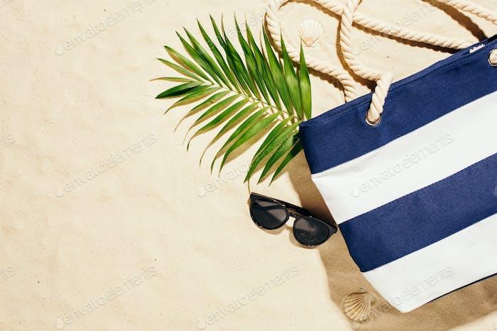 Beach blue bag and sunglasses on the sand