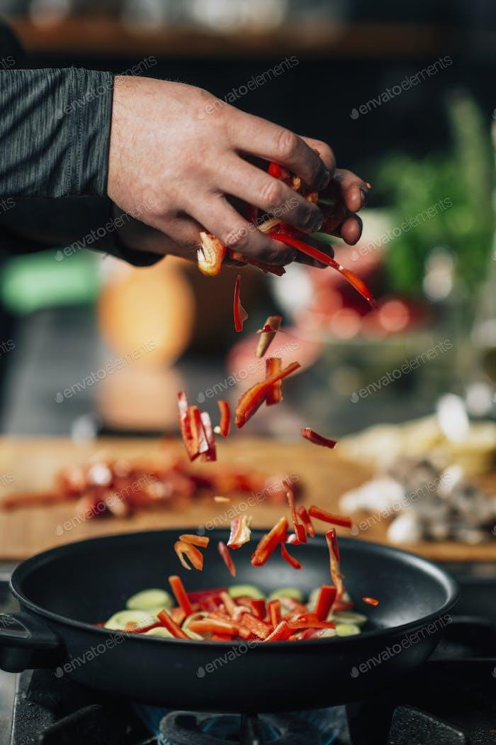 Vegan Restaurant Cooking - In Scheiben geschnittene rote Paprika in eine Pfanne geben