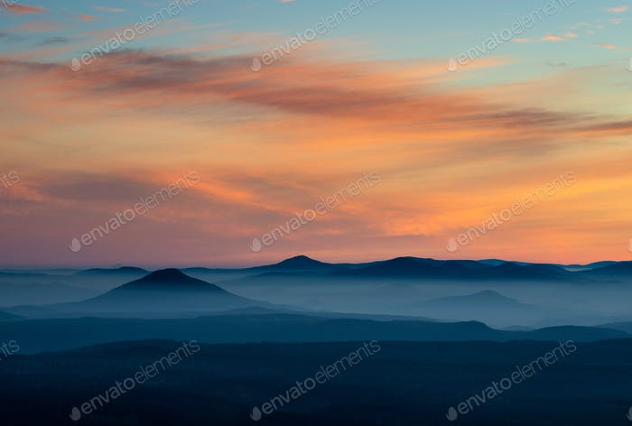Dramatic sunrise over beautiful mountain peaks. Decinsky Sneznik