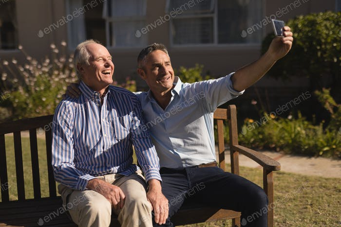 Side view of active senior Caucasian men taking selfie with mobile phone in the park