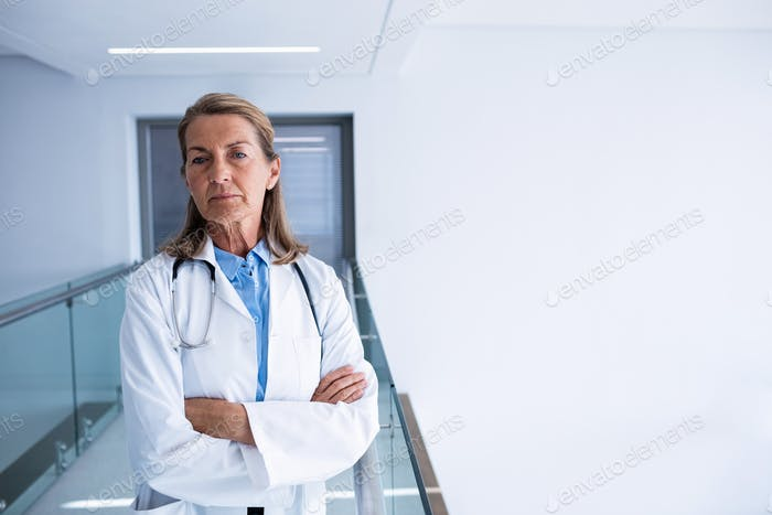Portrait of female doctor standing with arms crossed in passageway