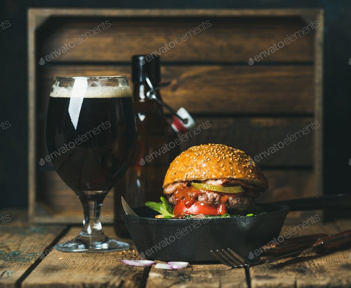 Beef burger with crispy bacon, fresh vegetables and dark beer