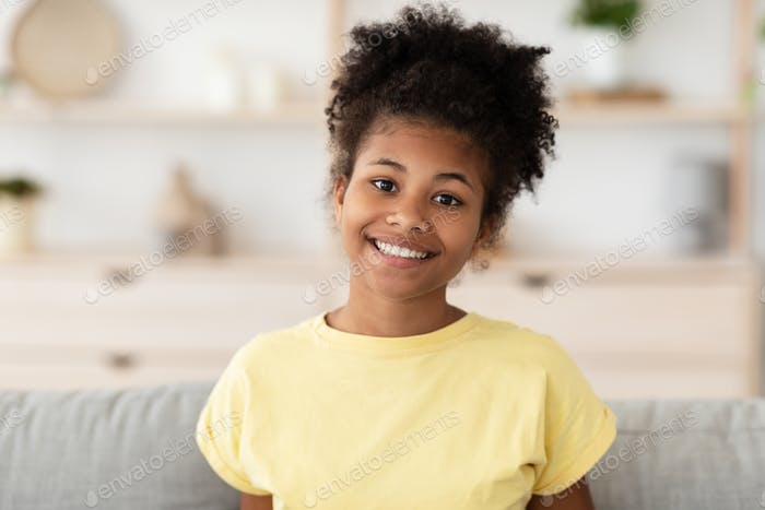 Cheerful African Girl Posing Sitting On Sofa At Home