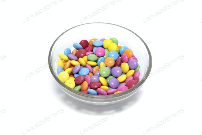 Bright colorful candy in glass bowl on white background