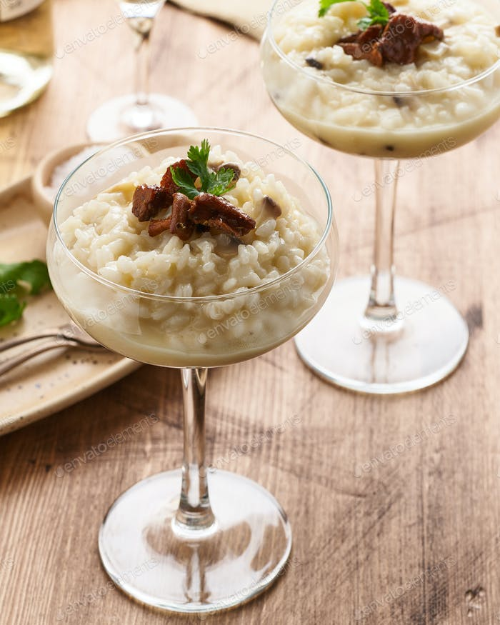 Risotto with mushrooms in wine glass. Unconventional unusual serving. Side view, vertical