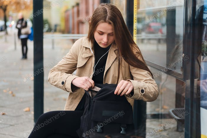 Beautiful girl in earphones looking something in backpack waiting public transport on bus stop
