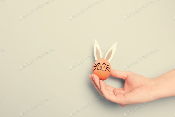 A hand holding little Easter bunny with paper ears