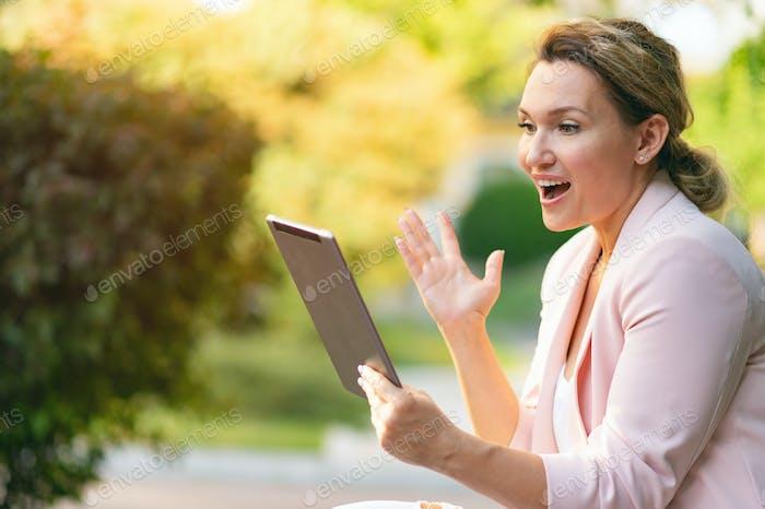 Взрослая женщина, общающаяся с людьми, использует планшет.
