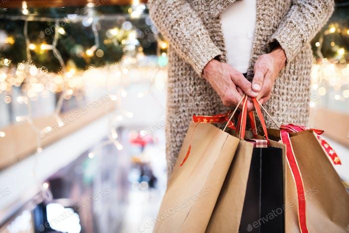 Seniorin mit Taschen, die Weihnachtseinkäufe machen.
