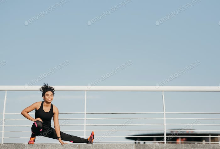Gymnastics, pilates and fitness outdoors. African american girl in sportswear doing warm-up