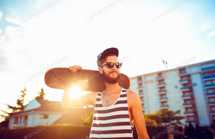 Man in sunglasses with a skateboard on a street in the city at s