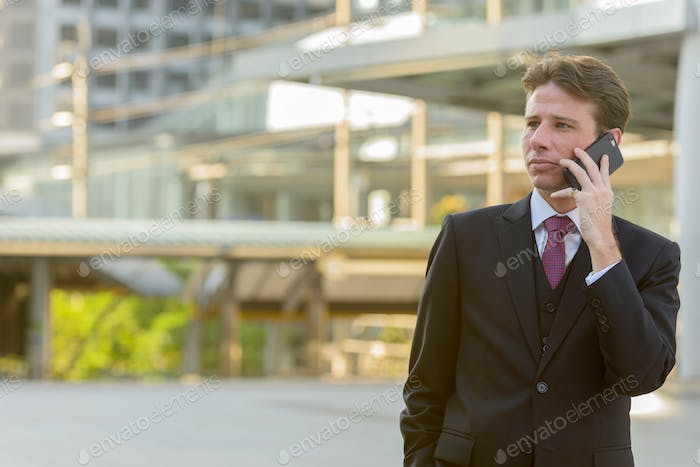 Businessman talking on mobile phone while thinking in front of m