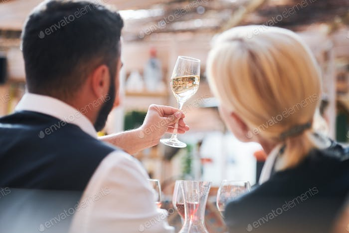 Two professional cavists studying characteristics of wine sample in flute
