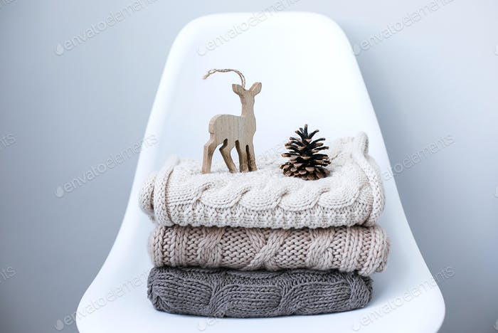 A stack of knitted sweaters on chair in Interior of the living room