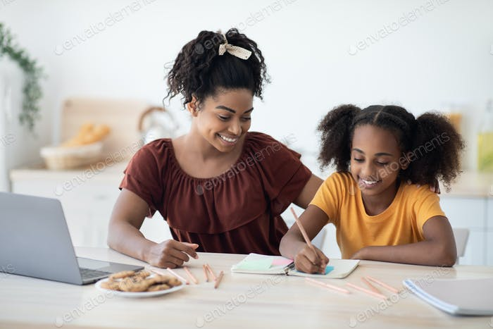Loving black mother and daughter drawing together at home