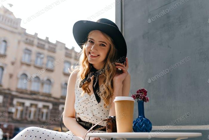 Elegant, aristocratic European girl in trendy modern dress smiling cute looking at camera at table
