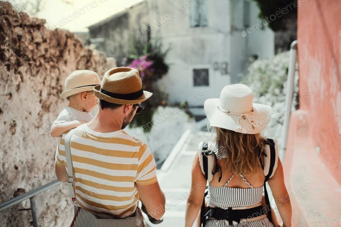A rear view of family with two toddler children walking in town on summer holiday.