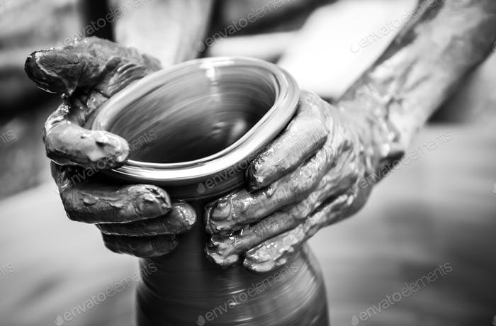 Hands of a man creating pottery on wheel, vintage style