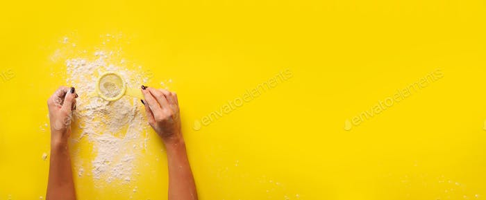 Female hand holding sieve flour on yellow background. Baking and cooking concept. Banner with copy