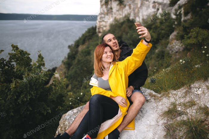 Happy hipster couple taking selfie on phone on top of rock mountain