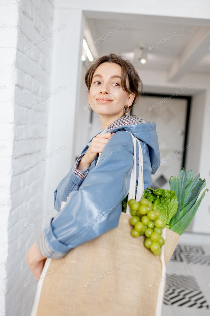 Woman coming home with shopping bag full of fresh food